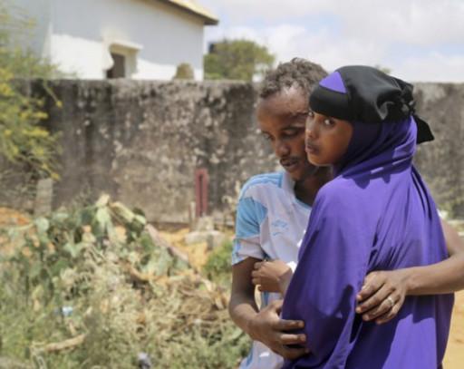 Zakariye Abdirisaq, à gauche, dont le père et la tante faisaient partie des centaines de personnes tuées dans l'attentat à la voiture piégée de Mogadiscio, est réconforté par sa cousine. Photographie par Mohamed Sheikh Nor / AP