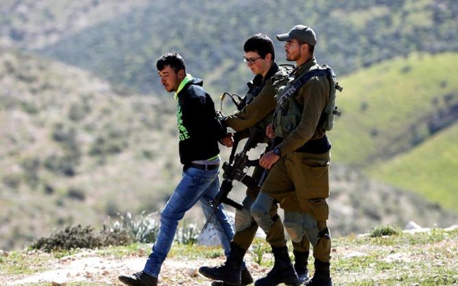 Des soldats israéliens arrêtent un Palestinien lors de la démolition de sa maison, pour laquelle il n'aurait pas obtenu de permis de construire, près de Yatta, en Cisjordanie occupée (Reuters)