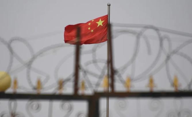 Le drapeau chinois flotte derrière des barbelés dans une cité de Yangisar, au sud de Kashgar, dans la région occidentale du Xinjiang en Chine (4 juin 2019). Greg Baker/AFP