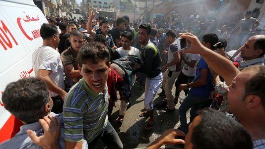 Des Palestiniens prennent en charge un des corps des personnes tuées lors du raid israélien, ce vendredi 27 juin 2014 à Gaza. [MOHAMMED SABER - Keystone], rts.ch