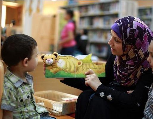 Une mère palestinienne lit une histoire à ses enfants lors d'un atelier de lecture estival (AFP)