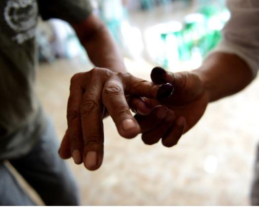 Un fonctionnaire électoral aide un électeur à appliquer de l'encre sur son doigt, dans un bureau de vote à Kuta, sur l'île touristique indonésienne de Bali, le 9/12/2015. L'Indonésie est la plus grande démocratie à majorité musulmane au monde.