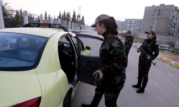 Les membres de l'Armée de Défense nationale inspectant un taxi dans le Wadi Dahab, une zone alaouite de Homs qui a été la récente cible d'attentats à la voiture. Photo : Anwat Amro/AFP/Getty Images